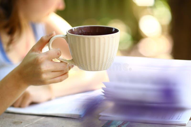 Menina adolescente com fim do copo de chá da posse do livro acima da foto imagens de stock royalty free