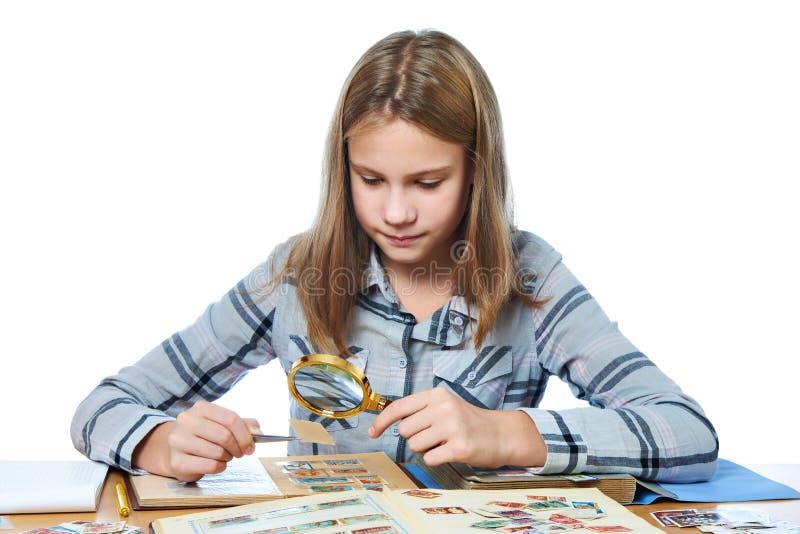 A menina adolescente com lente de aumento olha sua coleção de selo isolada imagens de stock