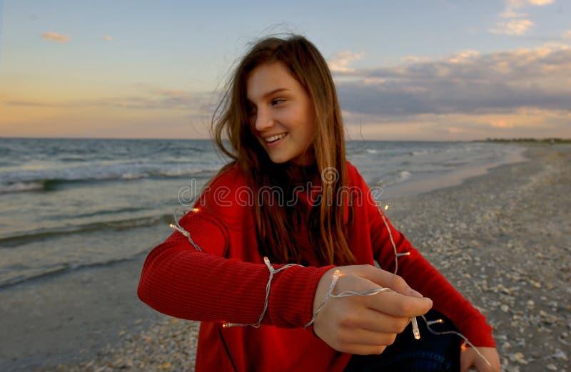 Menina adolescente com luzes na praia fotografia de stock