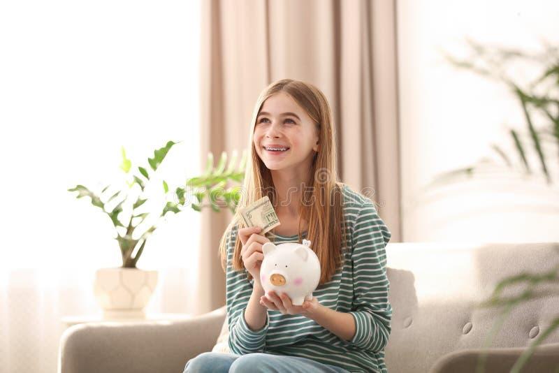 Menina adolescente com mealheiro e dinheiro imagens de stock royalty free
