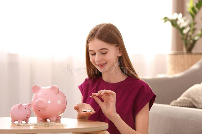 Menina adolescente com mealheiros e dinheiro imagens de stock