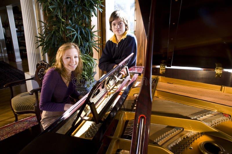 Menina adolescente com o irmão pelo piano imagem de stock royalty free