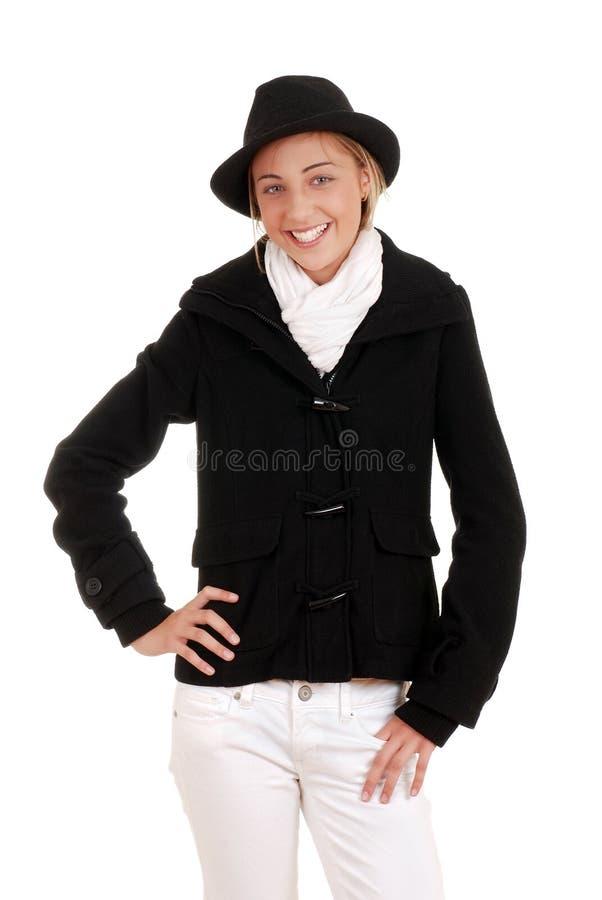 Menina adolescente com o revestimento e o chapéu pretos do inverno fotografia de stock