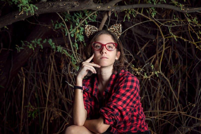 A menina adolescente com orelhas do leopardo senta-se contemplativa na frente de um T foto de stock