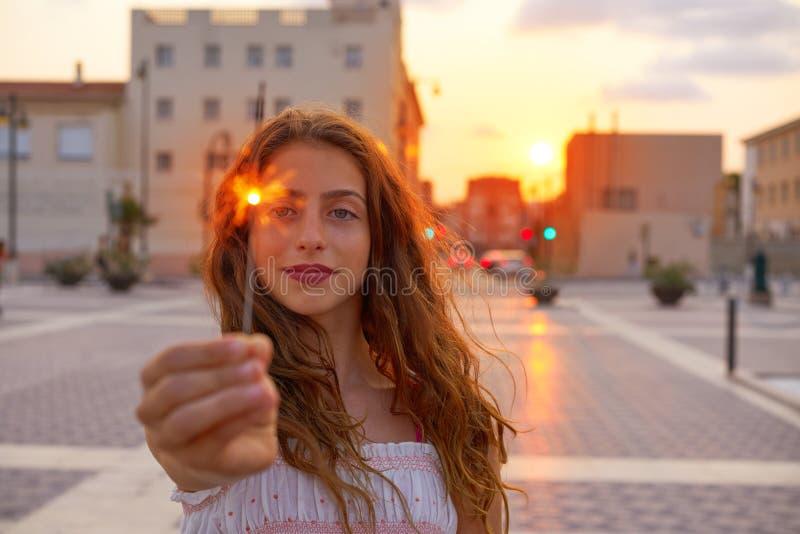 Menina adolescente com os chuveirinhos no por do sol na cidade fotografia de stock royalty free