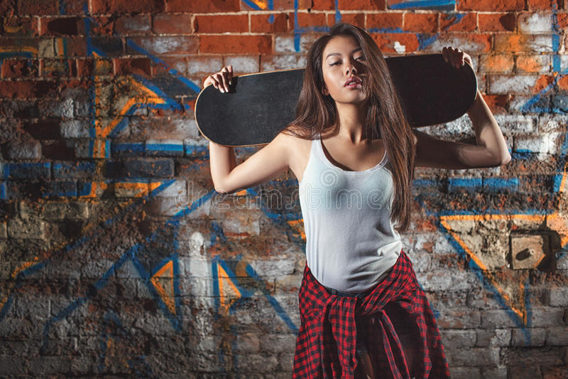Menina adolescente com placa do patim, estilo de vida urbano foto de stock royalty free