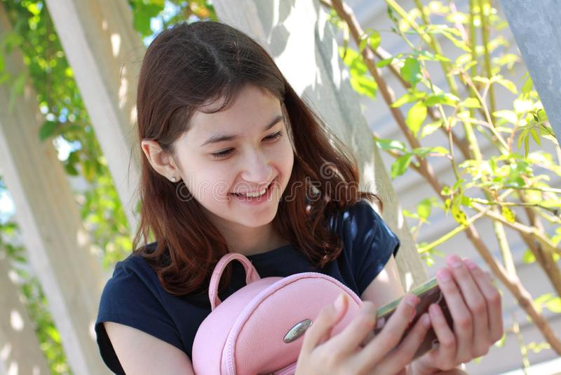 Menina adolescente com telefone m?vel Retrato de uma menina com uma trouxa em um banco de madeira no parque foto de stock