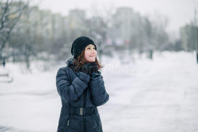 Menina adolescente congelada A criança aquece-se, as mãos abraçadas a sua cara Retrato de uma menina bonita imagem de stock
