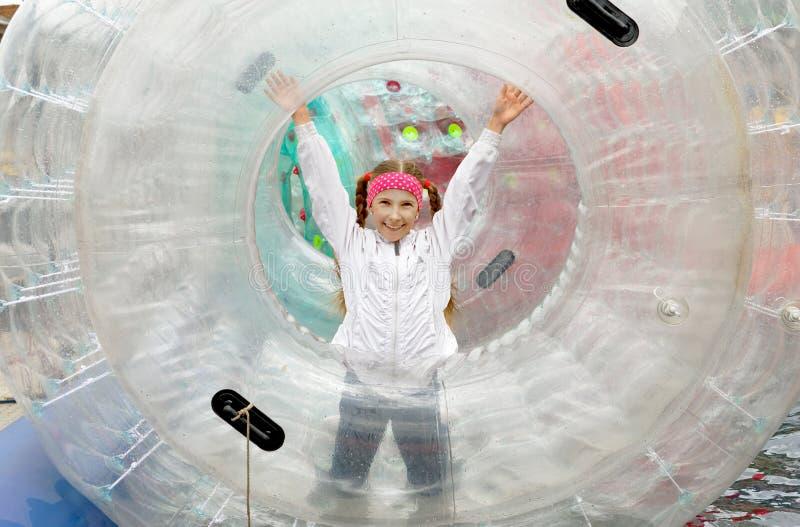 A menina adolescente corre felizmente dentro de um grande cilindro-zorb inflável foto de stock royalty free