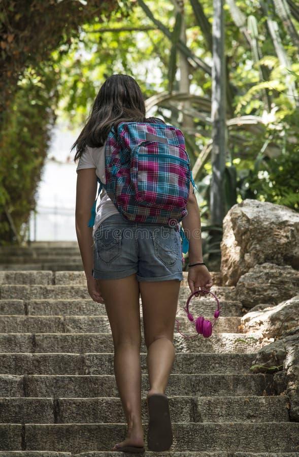 Menina adolescente da escola com uma trouxa no seu para trás e em fones de ouvido imagem de stock