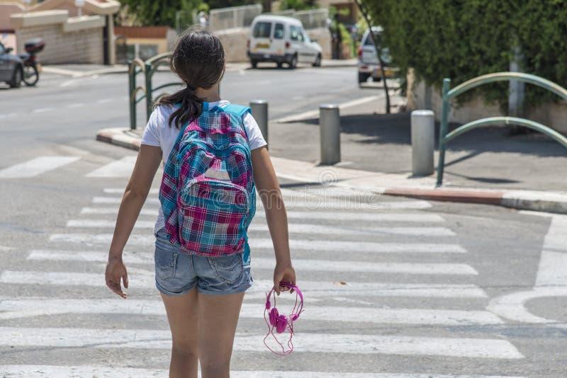 Menina adolescente da escola com uma trouxa no seu para trás e em fones de ouvido imagem de stock royalty free