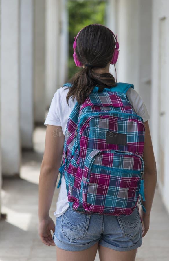 Menina adolescente da escola com uma trouxa no seu para trás e em fones de ouvido imagens de stock