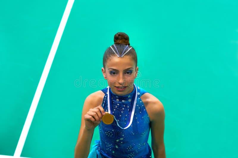 A menina adolescente da ginástica do medalheiro guarda a medalha imagem de stock royalty free