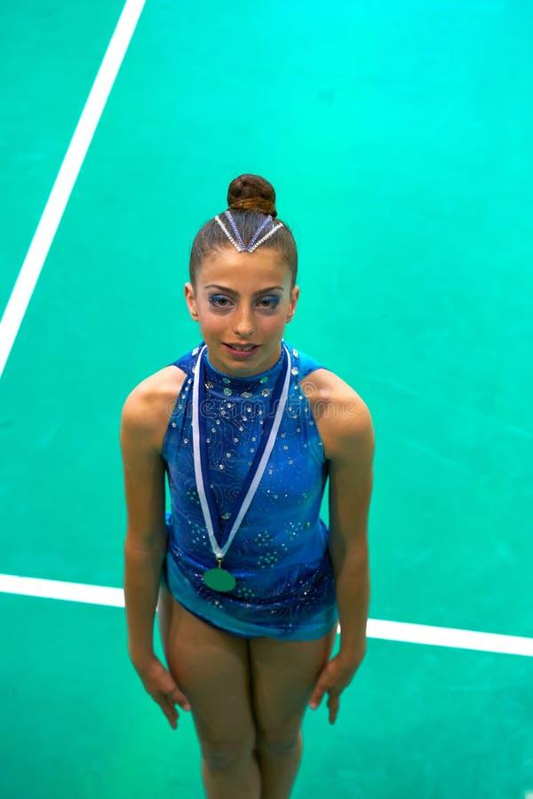 A menina adolescente da ginástica do medalheiro guarda a medalha foto de stock royalty free
