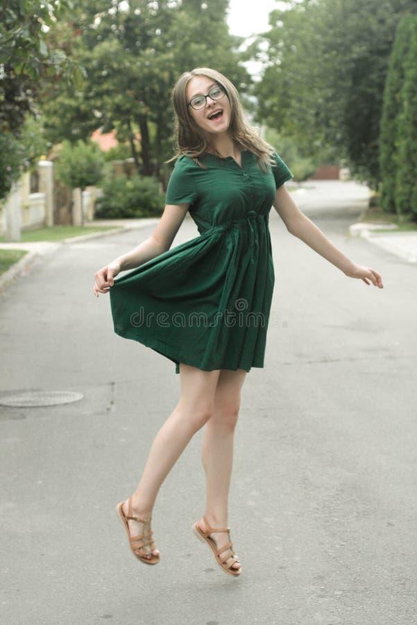 Menina adolescente da idade de Beautyful no vestido verde, saltando ?rvore no campo Mulher feliz livre foto de stock