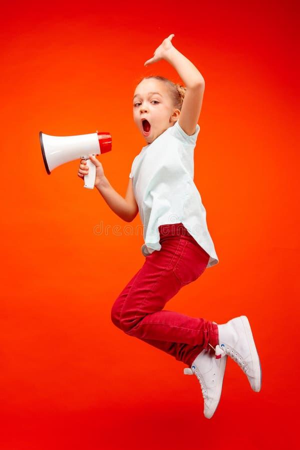 Menina adolescente da jovem criança bonita que salta com o megafone sobre o fundo vermelho fotografia de stock royalty free