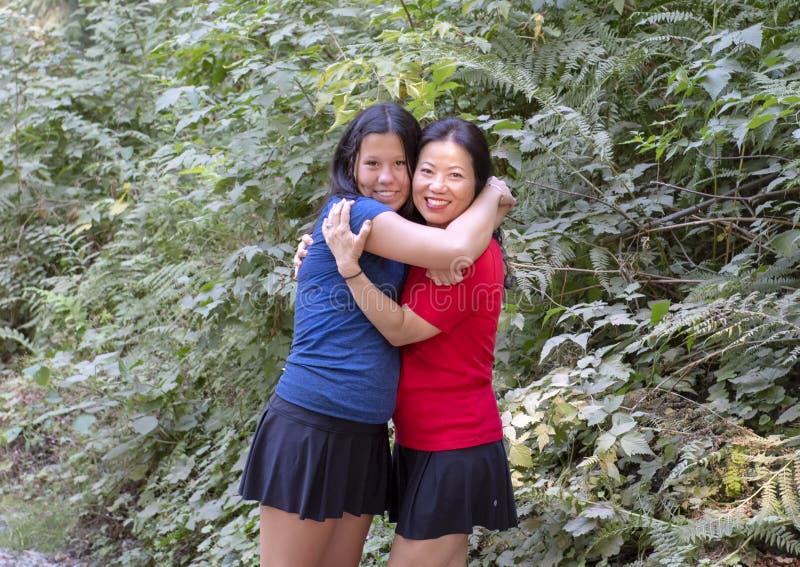 Menina adolescente de Amerasian no abraço afetuoso com sua mãe coreana, parque de Snoqualmie, estado de Washington imagem de stock royalty free