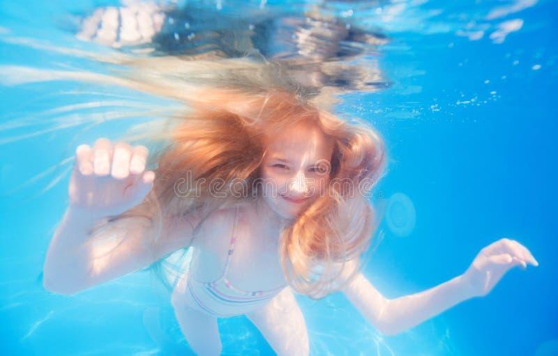 Menina adolescente de cabelo loura de sorriso debaixo d'água fotos de stock