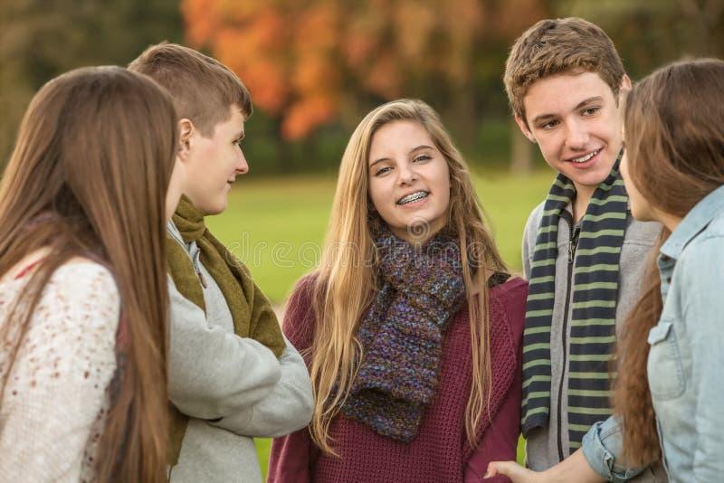 Menina adolescente de sorriso com amigos imagens de stock