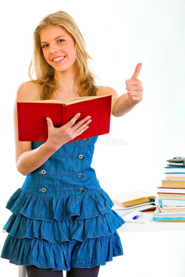 Menina adolescente de sorriso com o livro que mostra os polegares acima imagem de stock royalty free