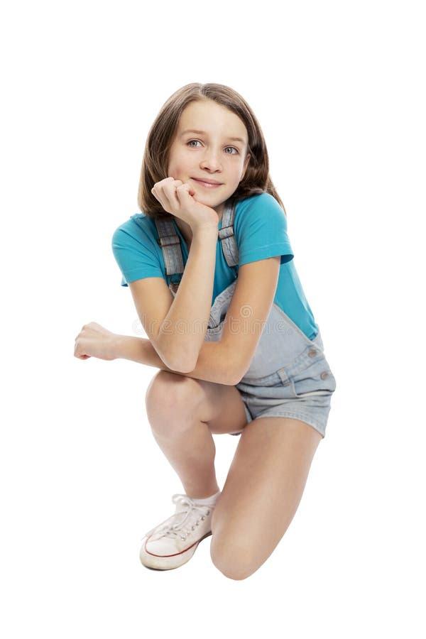 Menina adolescente de sorriso em ocupas dos macacões da sarja de Nimes Isolado em um fundo branco fotos de stock royalty free