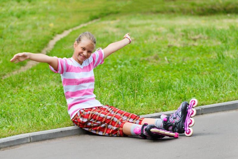 Menina adolescente de sorriso em patins de rolo foto de stock