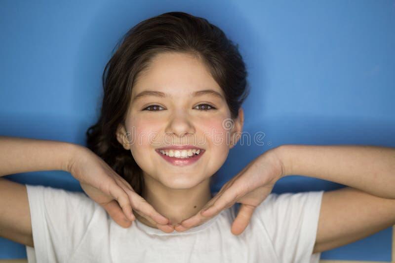 Menina adolescente de sorriso feliz bonita sobre o fundo azul foto de stock