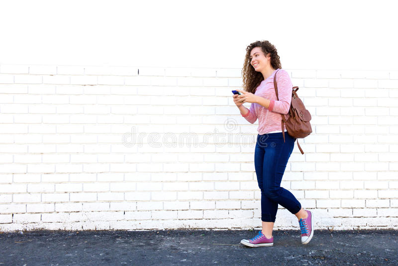 Menina adolescente de sorriso que anda com telefone celular e trouxa foto de stock