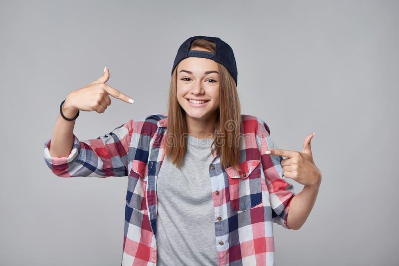 Menina adolescente de sorriso que aponta nsi mesma foto de stock royalty free