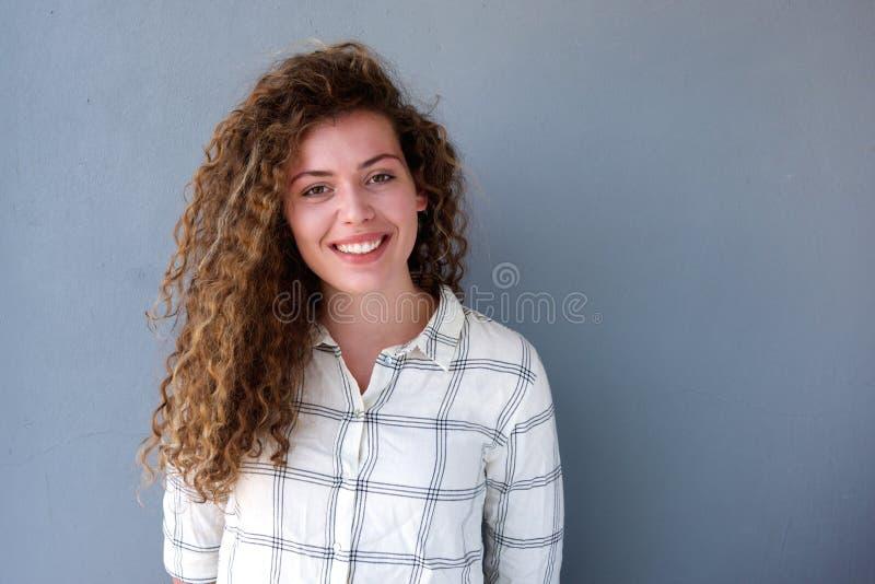 Menina adolescente de sorriso que está contra o fundo cinzento imagem de stock