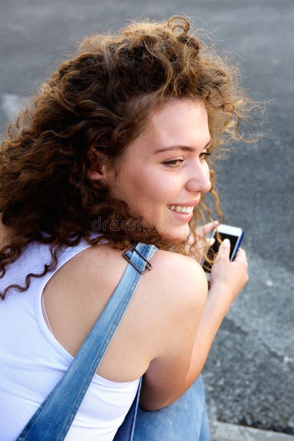 Menina adolescente de sorriso que guarda o telefone celular e o assento fotografia de stock