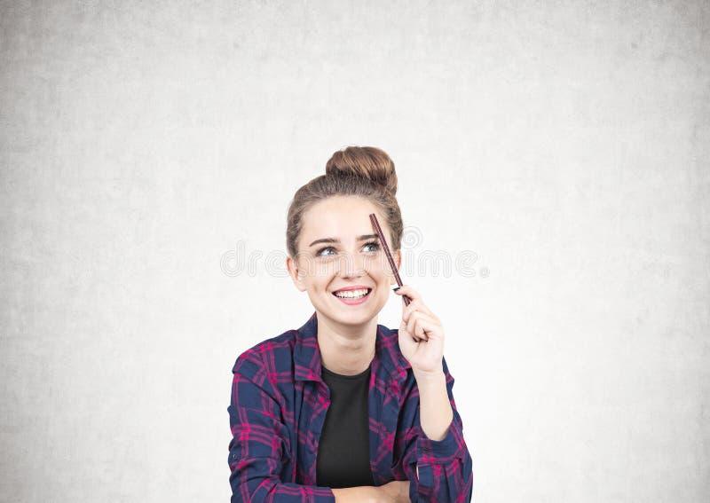 Menina adolescente de sorriso que pensa, lápis, concreto foto de stock