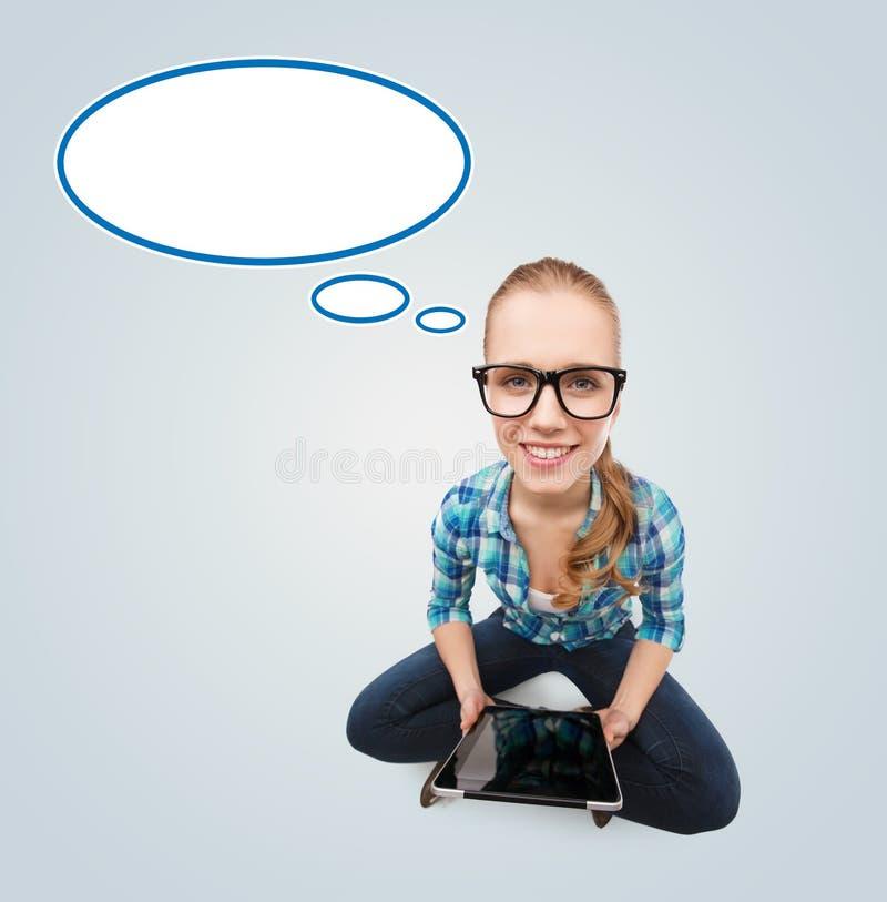Menina adolescente de sorriso que senta-se no assoalho com PC da tabuleta fotografia de stock