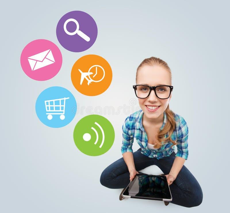 Menina adolescente de sorriso que senta-se no assoalho com PC da tabuleta fotos de stock
