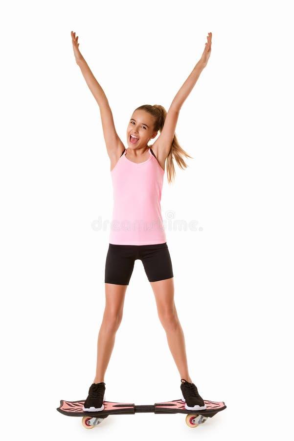 Menina adolescente desportiva alegre que está no waveboard com mãos acima, isolado fotos de stock