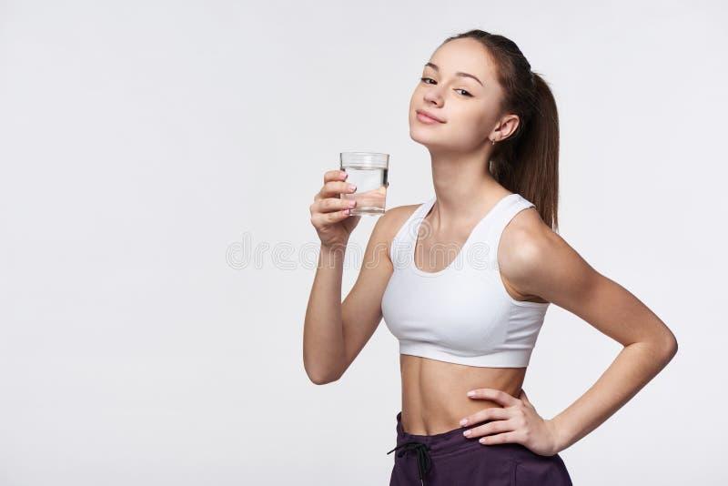 Menina adolescente desportiva com vidro da água fotos de stock royalty free