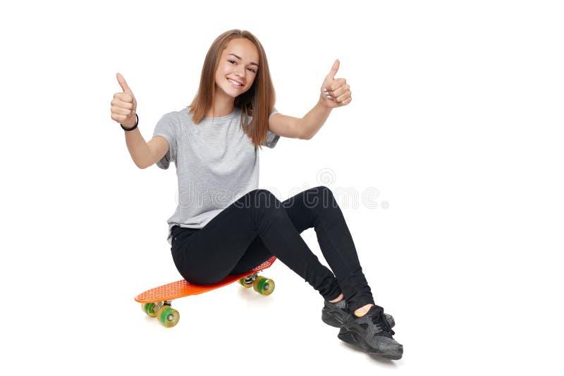 Menina adolescente do comprimento completo que senta-se na placa do patim imagens de stock