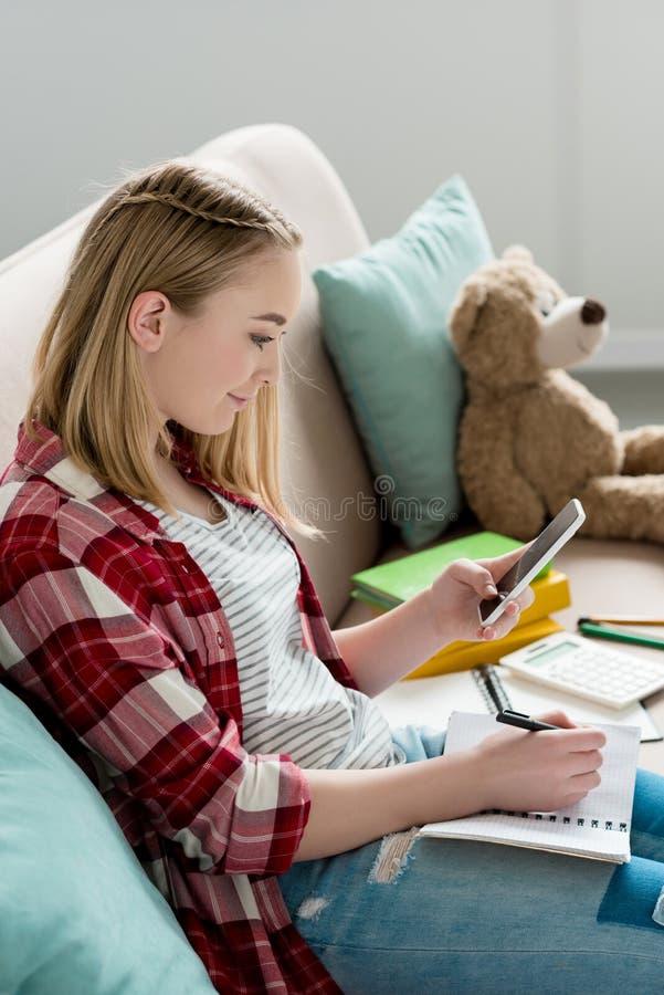 menina adolescente do estudante que faz trabalhos de casa no sofá imagem de stock royalty free