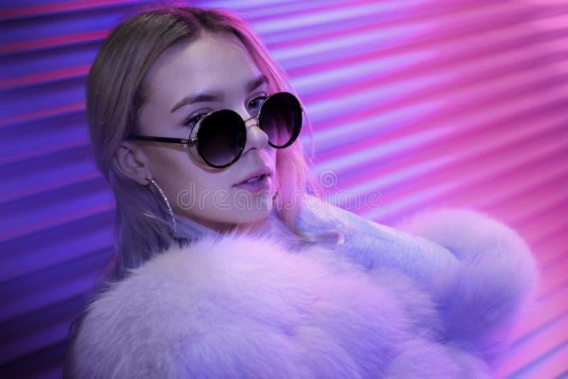 Menina adolescente do moderno na pele à moda dos vidros que levanta no fundo claro de néon da rua foto de stock royalty free