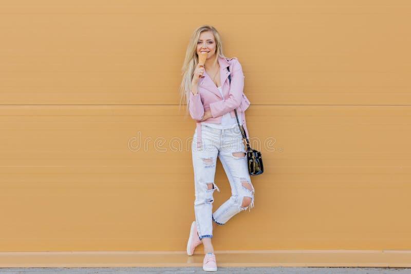 Menina adolescente do moderno novo surpreendente engraçado bonito bonito que come o cone de gelado, risos felizes, vestuário desp imagem de stock
