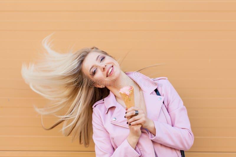 Menina adolescente do moderno novo surpreendente engraçado bonito bonito que come o cone de gelado, risos felizes, vestuário desp imagem de stock royalty free