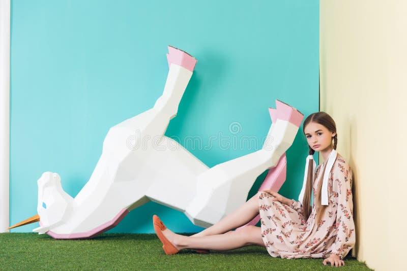 menina adolescente elegante bonita que levanta com o unicórnio grande de cabeça para baixo imagem de stock royalty free