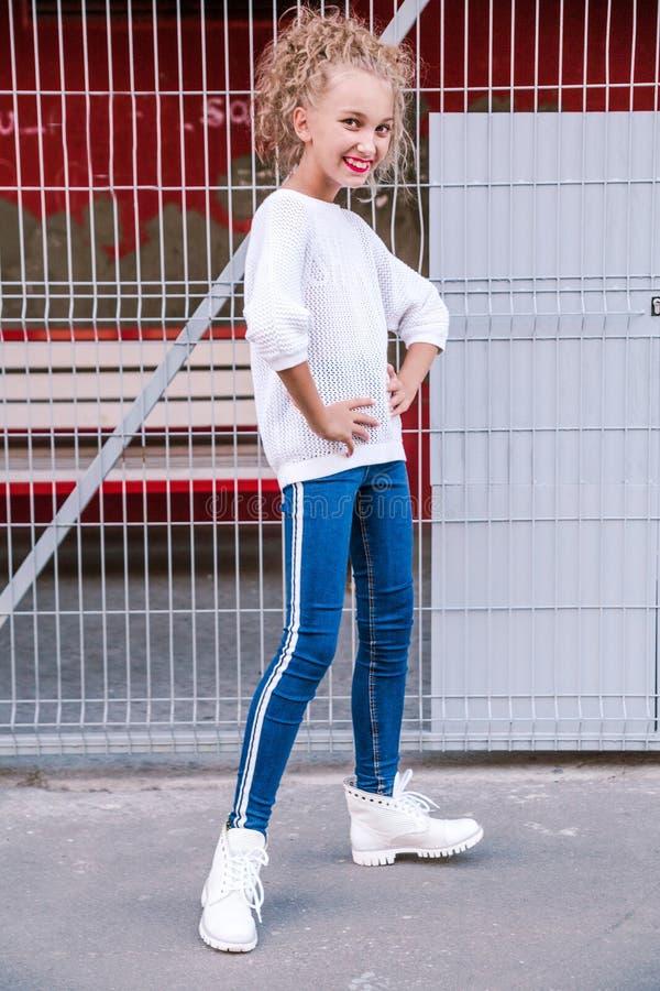 Menina adolescente elegante e feliz que levanta contra um fundo de uma construção e de uma estrutura fotos de stock royalty free