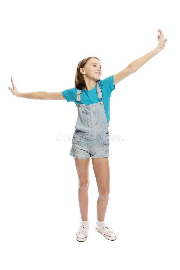 Menina adolescente em macacões da sarja de Nimes em uma pose de voo, altura completa Isolado em um fundo branco fotografia de stock royalty free