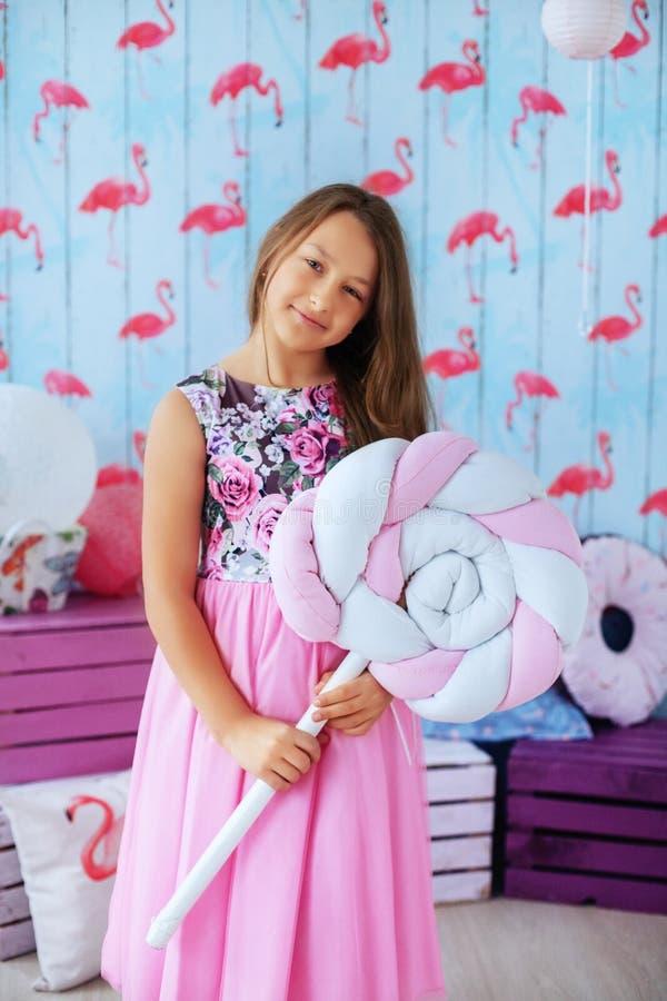 Menina adolescente em um vestido cor-de-rosa na sala O conceito da infância fotografia de stock