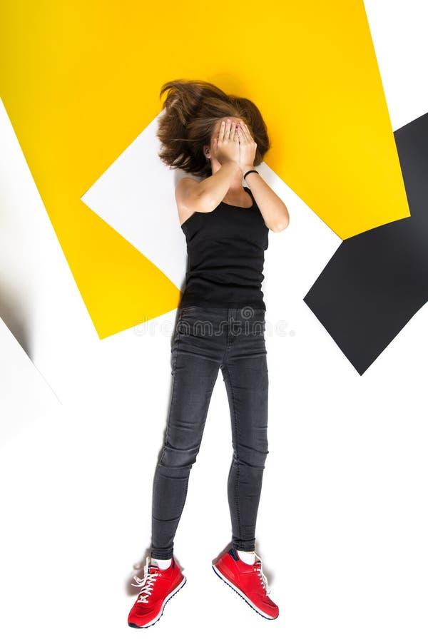 A menina adolescente encontra-se cobrindo sua cara com suas mãos Vista de acima Roupa escura, sapatas vermelhas fotos de stock