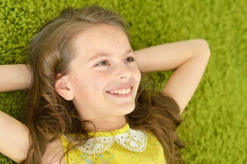 A menina adolescente encontra-se no tapete imagem de stock