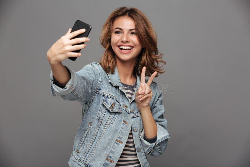 Menina adolescente engraçada no revestimento das calças de brim que mostra o gesto da paz quando taki imagens de stock
