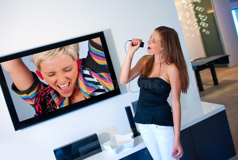 A menina adolescente escuta música e cantando fotografia de stock