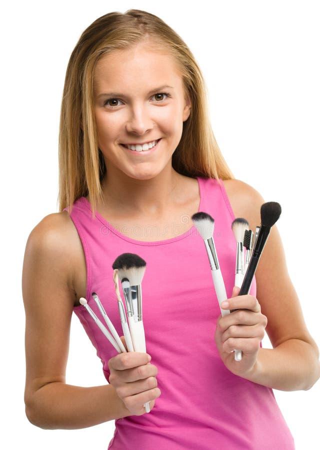 A menina adolescente está guardando escovas da composição fotos de stock